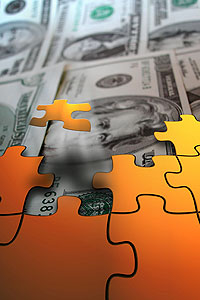 Picture of money being covered by pieces of a puzzle